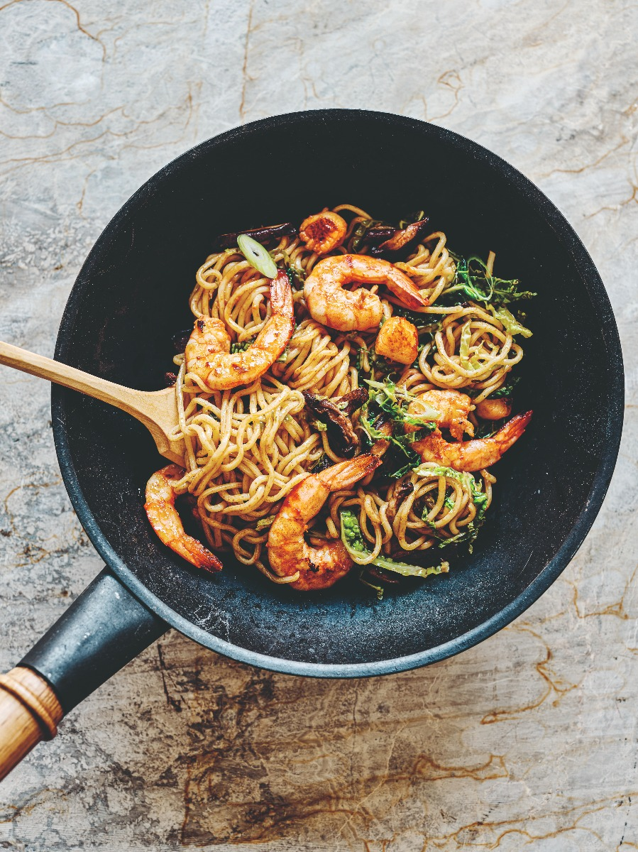 Prawns, scallops, cabbage and shiitake mushrooms with ramen noodles in a wok