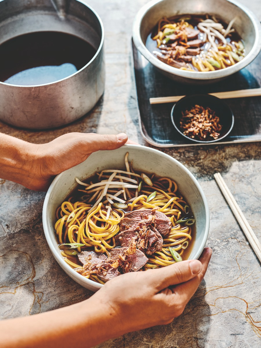 Two bowls of duck noodle soup, chopsticks and saucepan with broth
