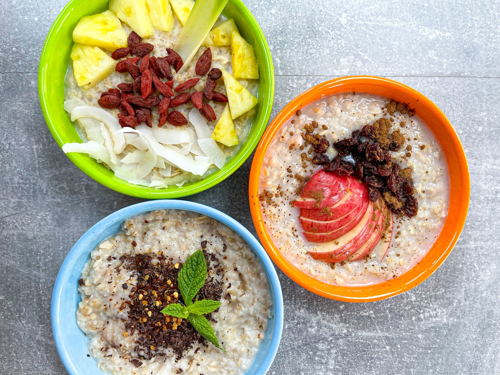 Three porridge bowls, one topped with pineapple and goji berries, another with apple, raisins and cinnamon and the last topped with dark chocolate and chilli.