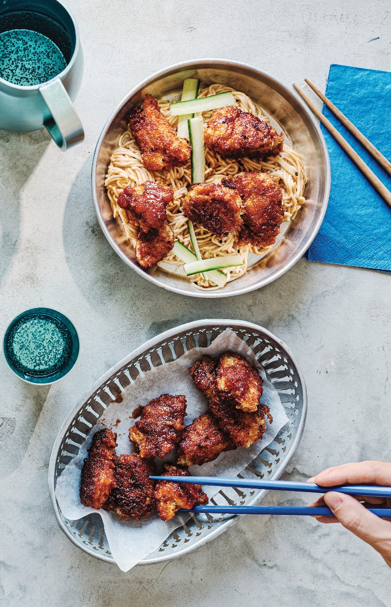 Korean fried sticky chicken on a bed of noodles served in a bowl